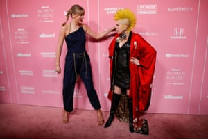Los Angeles, US. Taylor Swift greets Cyndi Lauper as they arrive on the red carpet for the Billboard Women in Music event