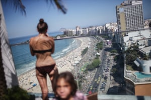 <strong>Rio de Janeiro</strong> People gather on an upscale hotel rooftop as protesters march below along Copacabana beach