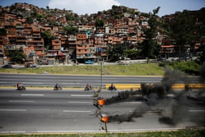 Motorcyclists drive past a burning roadblock during a rally in Caracas against Nicolas Maduro's government