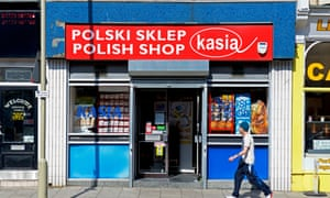 Man walking past Polish shop in Scarborough, North Yorkshire.