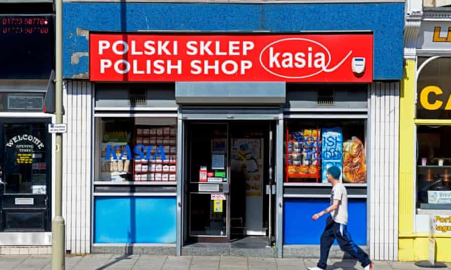 Man walking past Polish shop in Scarborough, North Yorkshire.