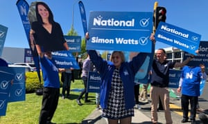 Judith Collins holds a National party hoarding at an intersection on Auckland's North Shore.