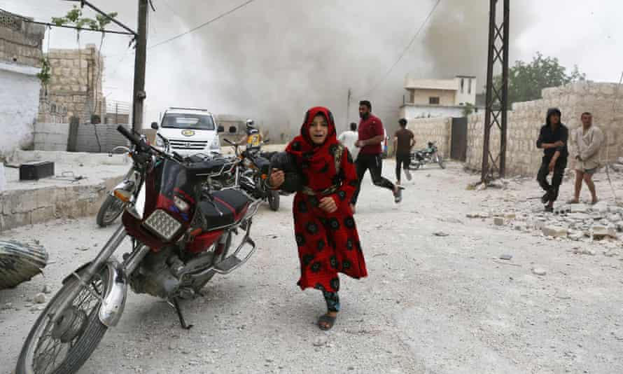 Syrians run for cover during an airstrike in Idlib on 30 May.