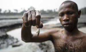 A fisherman displays his meagre catch from a creek near Goi in Ogoniland, Nigeria