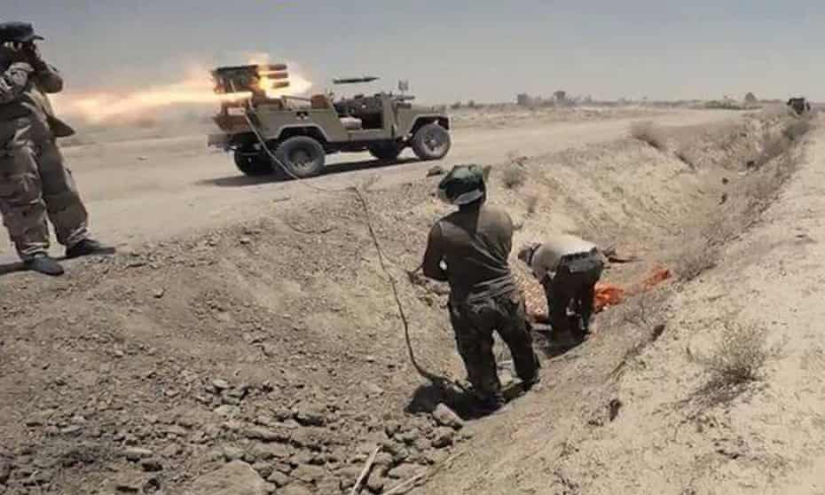 In this Tuesday, July 7, 2015 photo Iraqi security forces and allied Shiite militiamen launch rockets against Islamic State extremist positions in Saqlawiyah near Fallujah, Iraq.
