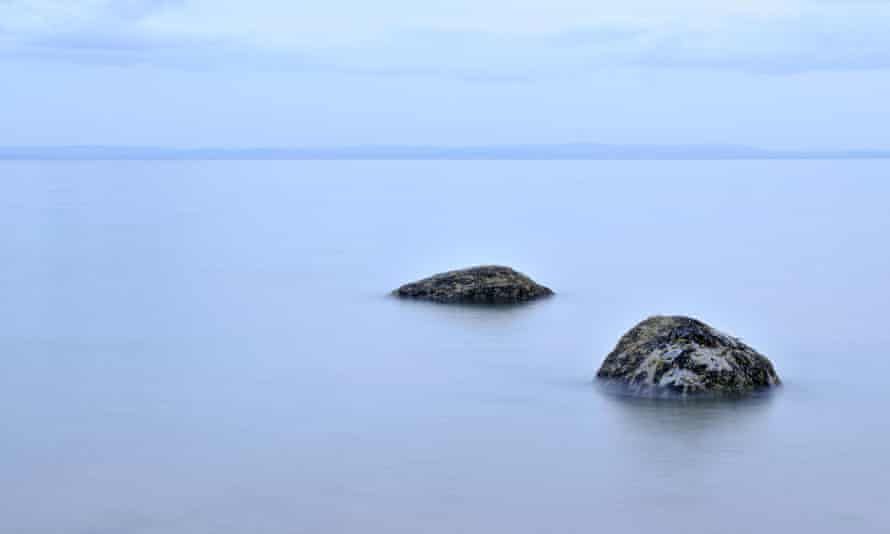 Partly submerged rocks in calm water at Largo Bay in Lower Largo, Fife, Scotland