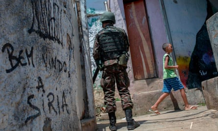 "A Brazilian army soldier patrols the Rocinha favela in Rio de Janeiro, Brazil on 11 October 2017 by a graffiti that reads in Portuguese ""Welcome to Syria""."