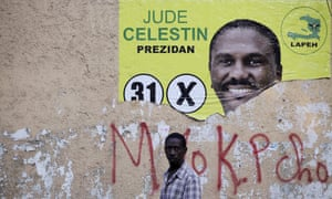A man walks next to a ripped electoral poster of presidential candidate Jude Celestin in Port-au-Prince.
