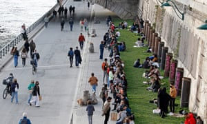 People gather on the banks of the Seine in Paris before the curfew which starts at 6 pm.