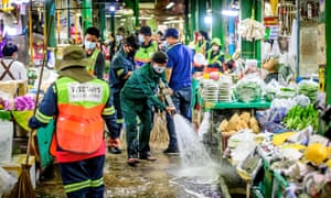Employees of the Bangkok Metropolitan Authority clean and disinfect the Yodpiman Flower Market in Bangkok on 6 January 2021, after the government imposed further restrictions due to the recent Covid-19 coronavirus outbreak.