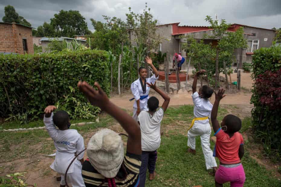 Natsiraishe Maritsa goes through taekwondo stretching drills with young children from her community