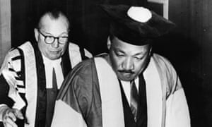 Dr. Martin Luther King, Jr., watched by Dr. Charles Bousenquet, signs the Degree Roll At Newcastle University after receiving an honorary Doctor of Civil Law degree, November 14, 1967.
