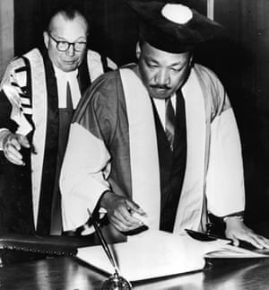 American civil rights leader Dr Martin Luther King, watched by Dr Charles Bousenquet, signs the degree roll At Newcastle University in 1967.