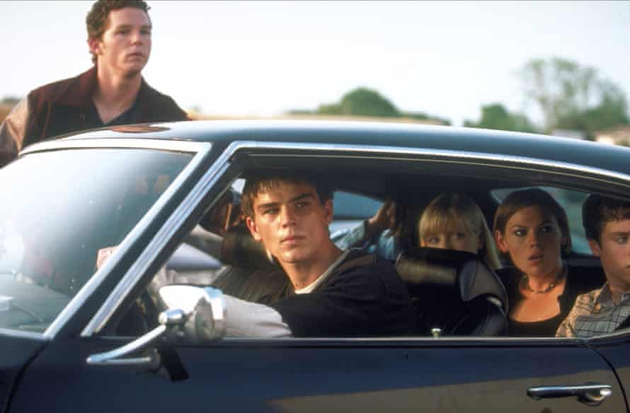 Teenagers in a car looking at something