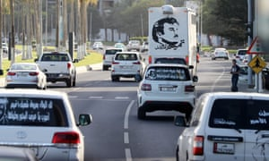 Portraits of Qatar's Emir Sheikh Tamim bin Hamad Al-Thani on the back of vehicles and text reading in Arabic: 'Tamim the glorious' in Doha amid the diplomatic crisis.