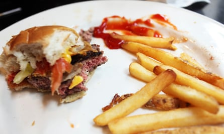Half-finished hamburger and fries