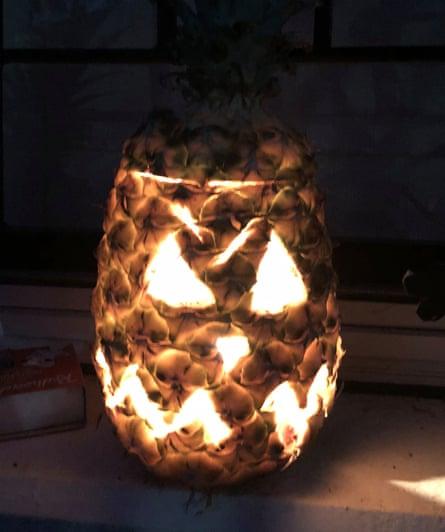 A pineapple carved like a jack-o-lantern