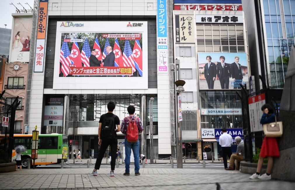 Dei pedoni a Tokyo assistono alla trasmissione in diretta dell'incontro tra Trump e Kim Jong-un. Credits to: Martin Bureau/AFP/Getty Images.