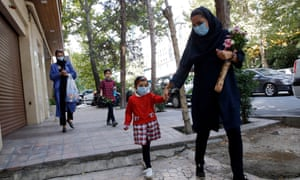 A schoolgirl wearing a face mask walks with her mother as she attends the first day of reopening  school in Tehran, Iran.