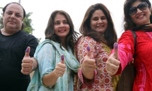 People show their marked thumbs after they cast their ballot at a polling station, during general elections in Karachi, Pakistan