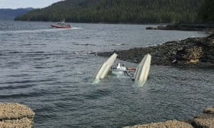US Coast Guard crew searches the waters around George Inlet near Ketchikan after two sightseeing planes collided midair. There have been four confirmed deaths, with two tourists missing.