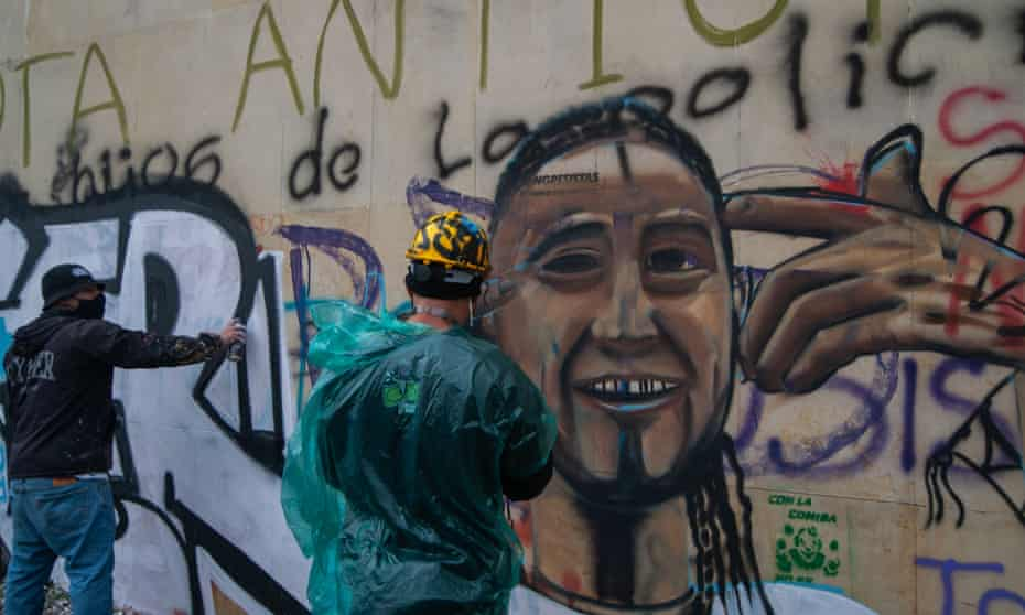 A demonstrator creates a mural with a portrait of Nicolás Guerrero.