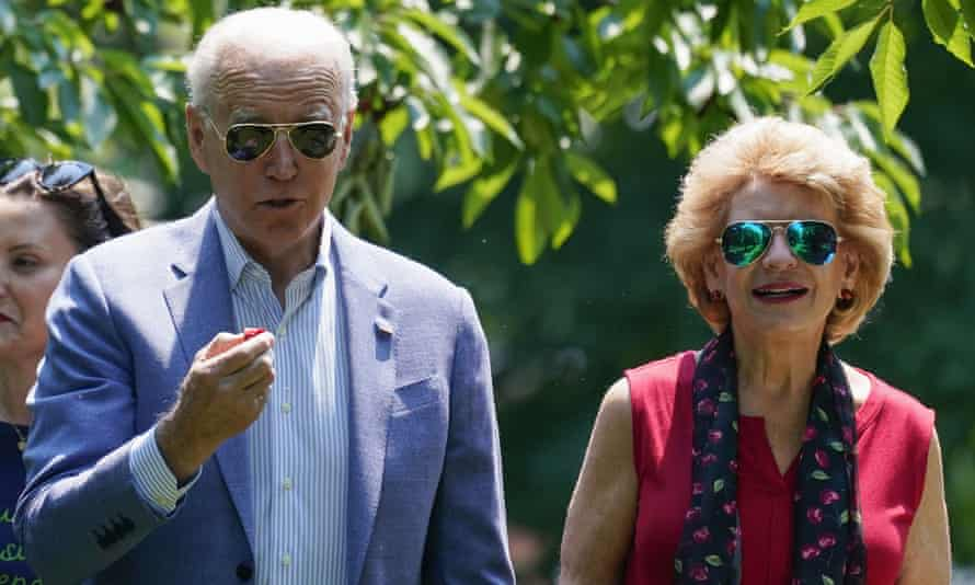 Joe Biden eats a cherry as he tours a fruit farm with Debbie Stabenow, a Democratic senator from Michigan.