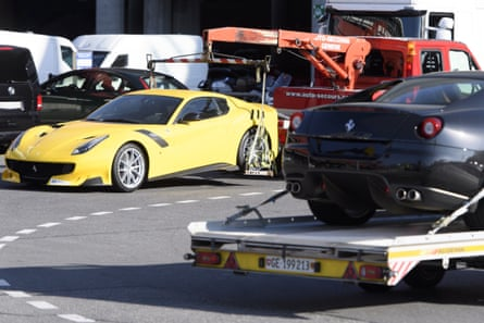 Two Ferraris belonging to Teodorin Obiang are towed off the freight zone by police at Geneva airport.