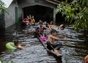 Narathiwat, Thailand, Children ride on a boat outside a house affected by floodwaters following heavy rains Sungai Kolok district