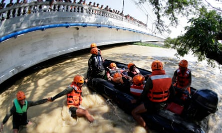 As bystanders look on from a bridge, Filipino soldiers rescue people caught in floodwaters in the town of Calumpit