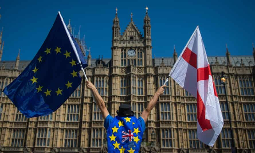 An anti-Brexit demonstrator holding EU and England flags outside the Houses of Parliament in London.
