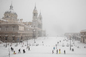 People enjoy the snow outside La Almudena Cathedral in Madrid.