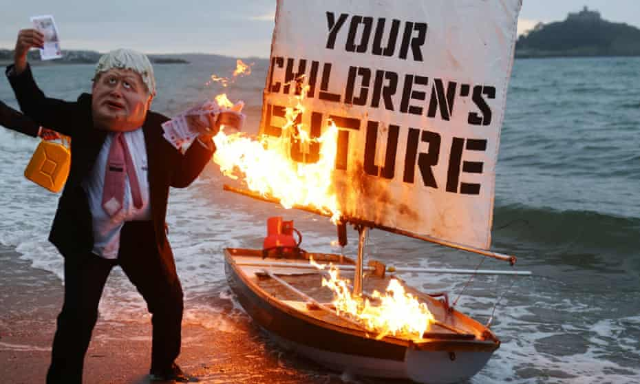 Two activists from Ocean Rebellion, one wearing a Boris Johnson mask and holding money, set a boat on fire during a demonstration ahead of the G7 summit in Cornwall.