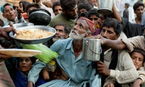 People affected by flooding in Pakistan's Sindh province in 2010 scramble for food distributed by the Pakistan military
