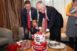 The Prime Minister Malcolm Turnbull with Craig Heatley and 3 year old Isobel Carroll, cut a cake for Red Nose Day
