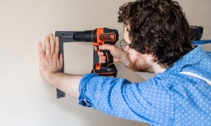 Tom Druker drilling a hole in the wall
