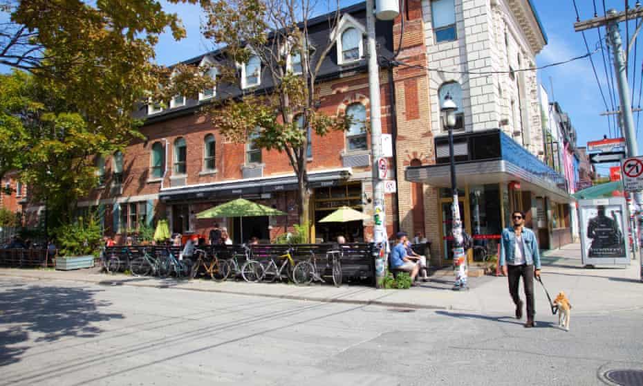 A man walks his dog past the Drake Hotel's sidewalk cafe, Toronto