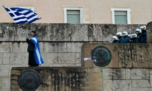 A priest waves a Greek flag outside the parliament building in Athens