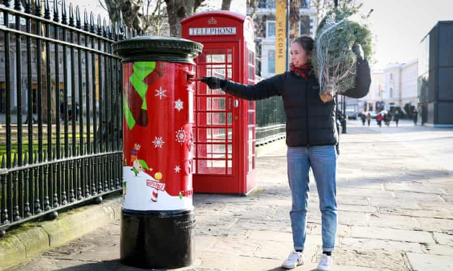 A woman posts a letter in a Christmas postbox