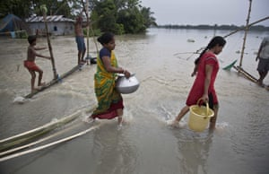 Women carry drinking water across a flooded road in Murkata village, east of Gauhati, Assam state, India.