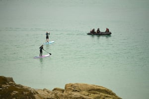 Paddleboarders watch as police in a rubber dinghy patrol the waters between St Ives and Carbis Bay