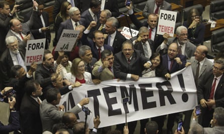 Deputies from opposition parties carry a banner that reads 'Temer Out!' during a vote by the lower chamber of Brazil's Congress in Brasilia, Brazil Wednesday.
