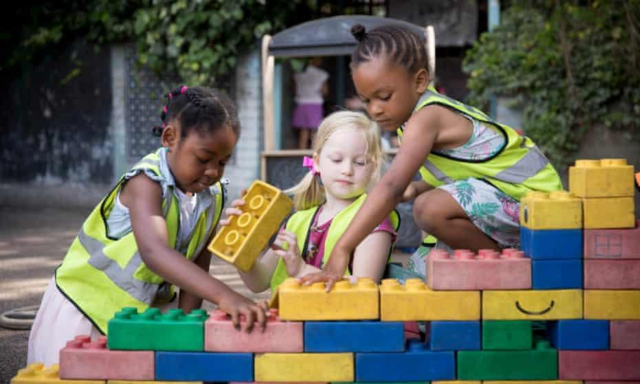 Three girls building a wall.