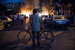 Damascus, August 2013: A cyclist watches the fire caused by an exploded mortar.