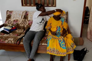 Khadjou adjusts her grandmother Madicke Mbengue's scarf, as they sit inside Sambe's family home