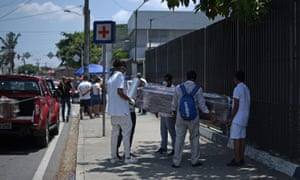 People wrap a coffin with plastic sheeting outside a hospital in Guayaquil, Ecuador