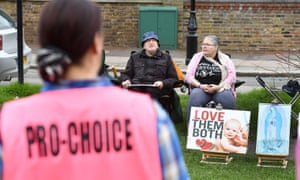 A pro-choice campaigner faces anti-abortion protesters outside a clinic in Ealing, west London