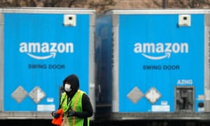 A worker in a face mask walks by trucks parked at an Amazon facility in Bethpage on Long Island, New York, on 17 March.