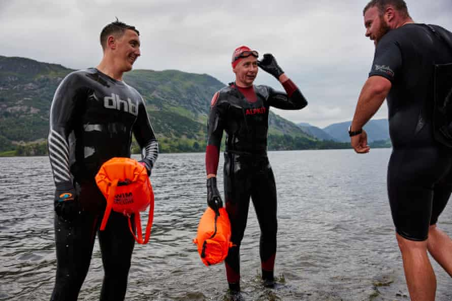 The three friends at the water's edge in wetsuits
