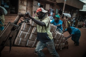 Laborers push goods on a chukudu